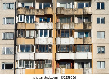 Dirty facade with balconies and windows.