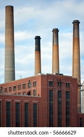 Dirty factory smoke stacks over an old brick building