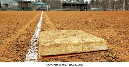 A dirty first base bag on a red dirt baseball diamond in a public park. The bright white baseline contrasted against the infield dirt leads from home to first.