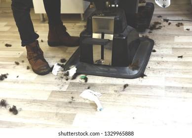 dirty floor in the Barber shop. hair on the salon floor. Haircut by scissors.