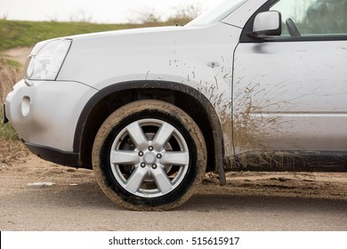 dirty front wheel of the off-road car with swamp splashes on a side panel and a front driver's door.