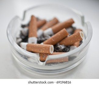 A dirty glass ashtray full of stubbed out cigarette butts
