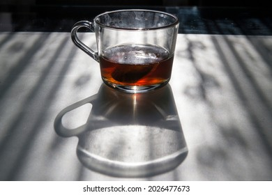 Dirty glass cup with tea and its shadow on a table