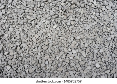 Dirty gravel ballast background. Small gray dusty broken stones texture. Top view