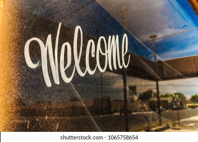 A dirty and grungy window with Welcome written on it and with the reflection on the street on a beautiful day of summer, Arizona.