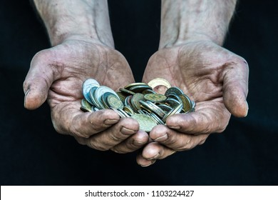 Dirty hands homeless poor man with many coins from different countries illustrating poverty in modern capitalism society