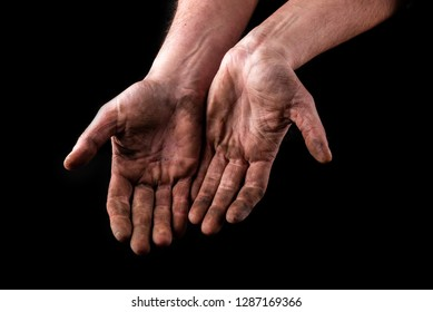 Dirty hands isolated on black background. Begging hands.