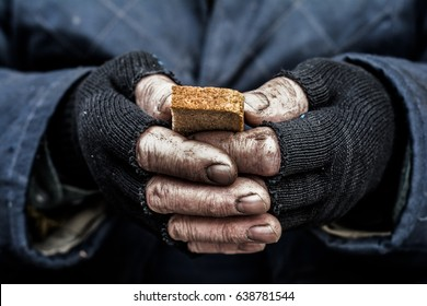 Dirty hands of a man clamped a piece of bread.