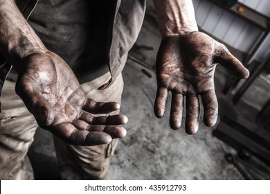 Dirty hands of mechanic at car station