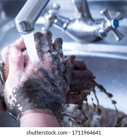 Dirty hands in the mud washing under the sink
