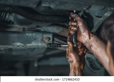 dirty hands of a technician while repairing a car