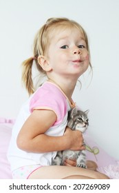 Dirty and happy little cute baby girl with gray small cat