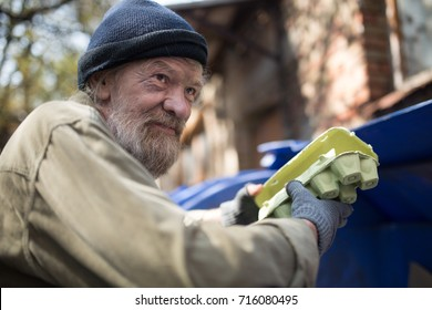 Dirty homeless man holding packing for eggs, standing by the trash can. Lifestyle of tramp, living in the streets.