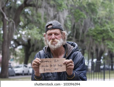 Dirty homeless man holding sign asking for help