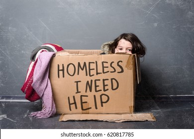 Dirty kid sitting in a paper box with a sign Homeless I Need Help. Old clothes, dark background. Social issues.