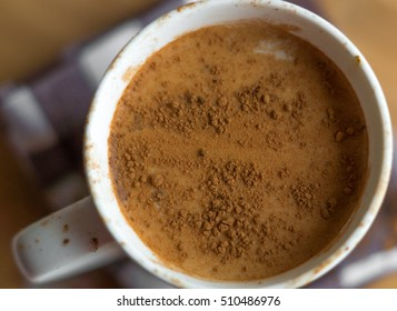 Dirty latte cup with cocoa powder