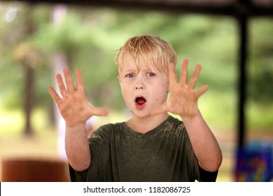 A dirty little boy child covered in sand is holding up his hands and appears to be saying no.