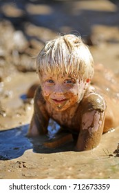 A dirty little boy child is laying in a large wet mud puddle, while playing outside.