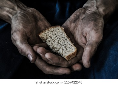 dirty male hands with a piece of bread, poverty, hunger