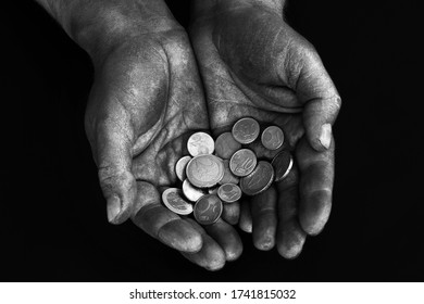 Dirty male hands of a worker keep the euro and euro cents on a dark background. Low-paid work. Money in the hands of a beggar. Low salary. Black and white