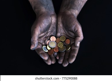 Dirty male hands of a worker keep the euro and euro cents on a dark background. Low-paid work. Money in the hands of a beggar. Low salary.