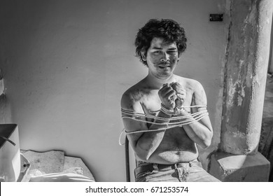 a dirty man captured as a slave tied with rope, soot covered on his body, his face show hopeless and fear, human trafficking concept