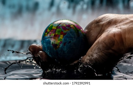 Dirty man's hand pulled the earth in the form of a globe out of the oil and is carefully holding It. Concept of eco friendly behavior, using natural resources and harming the environment