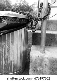 Dirty metal trash can chained to cement stairs in black and white.