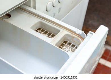 Dirty moldy washing machine detergent and fabric conditioner dispenser drawer compartment close up. Mold, rust and limescale in washing machine tray. Home appliances periodic maintenance.