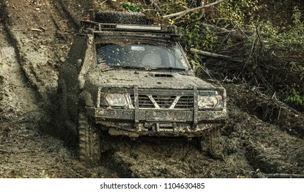 Dirty offroad car with nature on background. SUV covered with dirt on path covered with mud. Crossover driving through deep rut with puddle of mud. Extreme entertainment concept.