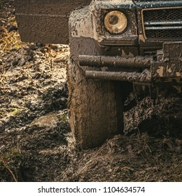 Dirty offroad tire covered with mud. Wheel in deep rut goes through mud and leaves trail. Extreme entertainment concept. Fragment of offroad car stuck in dirt, close up.