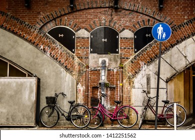 Dirty and Old Brick Wall. The strange old wall in the dark corners of the big cities. Dirty brick wall beside the train station in a big city, with a few bikes park beside the wall. Tokyo, Japan.