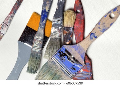 Dirty old brushes of paint, isolated on white canvas