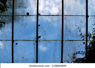 Dirty old greenhouse windows with a blue sky background