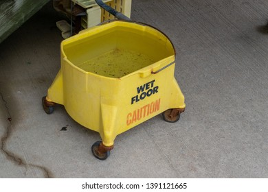 A dirty old mop bucket setting outside on a concrete patio.