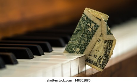 Dirty old one dollar bill stuck in a piano.- Hard times being a musician