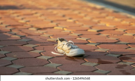 Dirty old shoe on the street floor. Damaged white shoe with no pair