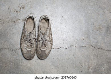 Dirty old shoes on concrete floor