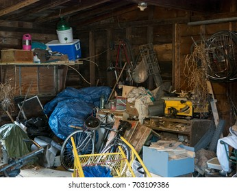 Dirty old wooden garage or shed filled with a chaotic mess of all kinds of stuff
