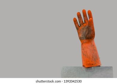 Dirty, orange rubber glove on a pole