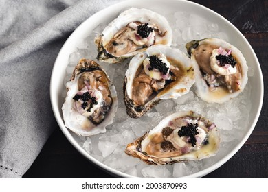 Dirty Oysters Served in a Bowl of Crushed Ice: Raw oysters topped with caviar, minced shallot, and creme fraiche
