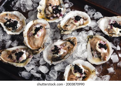 Dirty Oysters Served on a Bed of Crushed Ice: Raw oysters topped with caviar, minced shallot, and creme fraiche