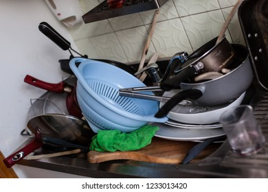 a lot of dirty pans, glasses and other kitchen utensils in a sink