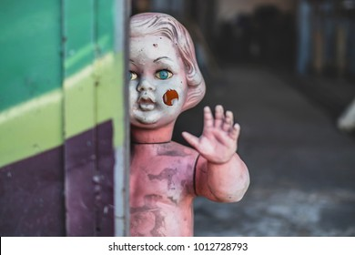 Dirty plastic naked baby doll standing by the door at the metal work shop looking eerie and hunted weaving at the customers