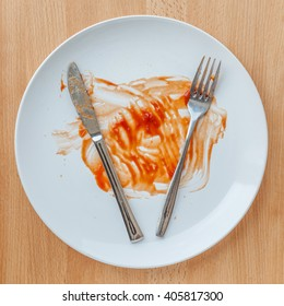 Dirty plate with knife and fork smeared with tomato sauce.