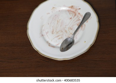 Dirty plate on a brown background. Natural wood desk.My cake's plate.