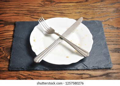 Dirty plate with silver knife and fork crossed on the dark blue board on the wooden background