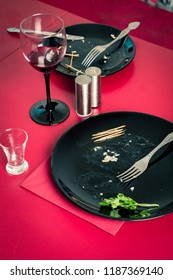 Dirty plates and an empty glass after dinner on the red table. A mess after eating