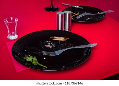 Dirty plates and empty glass after dinner on the red table