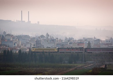 Dirty pollution. A train passes the old city of south Yunnan, China, land of coal. Coal mining with pipes on the mountain backgrounds, vegetable garden foreground. Environmental concept. Noise, Grain.